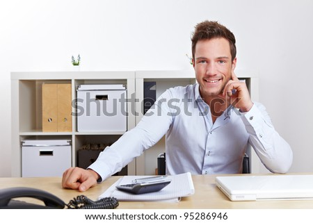 Happy young business man sitting at desk in office