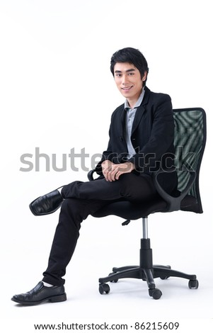 Happy young business man sitting in chair - stock photo