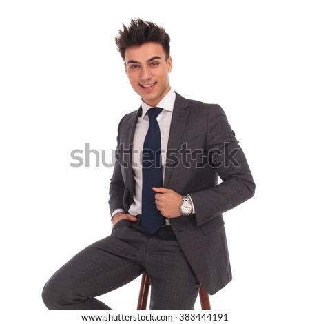 happy young business man sitting on a chair and smiles to the camera on white background