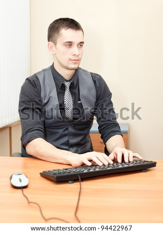 Happy young business man using computer and enjoying work