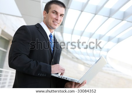 Happy young business man using laptop at office building - stock photo