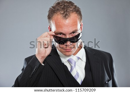 Happy young business man with short hair wearing dark suit with white shirt and purple tie. Wearing dark sunglasses. Tough guy. Studio shot isolated on grey background.