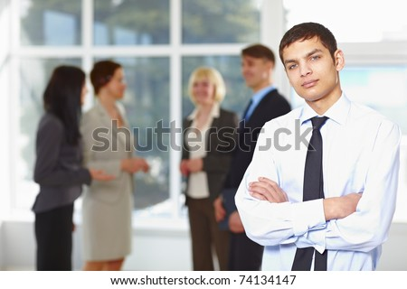Happy young business man with team mates discussing in the background - stock photo