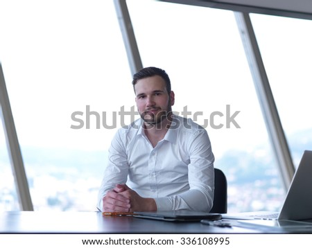 happy young business man work and relax at modern bright office interior, hipster with beard at workplace - stock photo