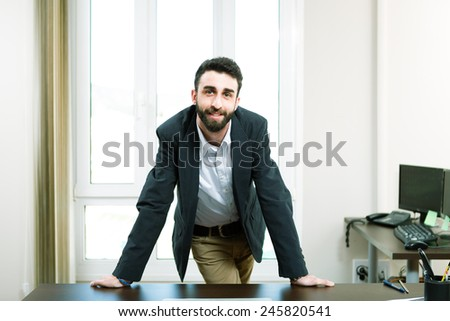 happy young business man work in modern office on computer leaning on his desk