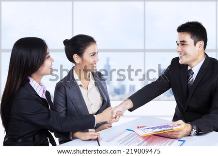 Happy young business partners shaking hands at meeting  - stock photo