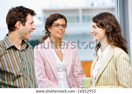 Happy young business people drinking coffe and talking at office in front of window, smiling. - stock photo