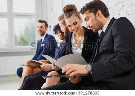 Happy young business people talking before job interview, assessment or test, exam at university - stock photo
