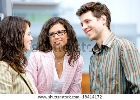 Happy young business people talking in front of office window, smiling, friendship. - stock photo