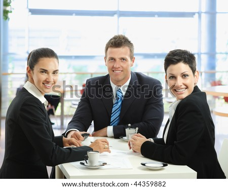 Happy young business people talking on meeting at coffee table, smiling.