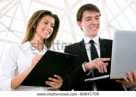 Happy young business people working together in holl a modern office building - stock photo
