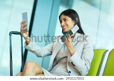 happy young business traveller taking selfie with smart phone while waiting for her flight at airport - stock photo