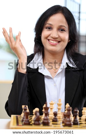 Happy young business woman playing chess - stock photo