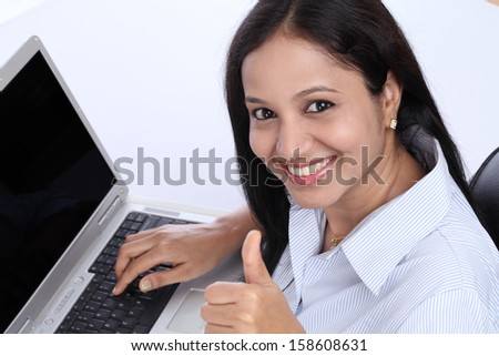 Happy young business woman showing thumbs up against white background
