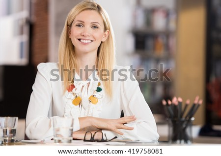 Happy young business woman sitting at the desk. Beautiful blonde businesswoman smiling and looking at camera. Portrait of attractive designer smiling at camera in office. Happy secretary at desk.  - stock photo