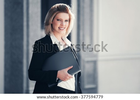 Happy young business woman with a folder at office building - stock photo