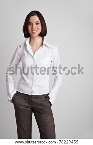 Happy young business woman with her hands in her pockets - stock photo