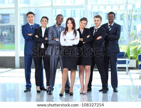 Happy young business woman with her team in background