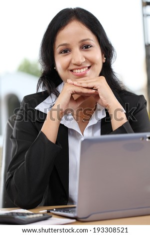 Happy young business woman working at office