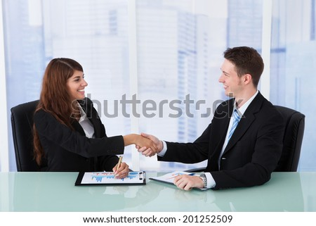 Happy young businessman and businesswoman shaking hands at office desk