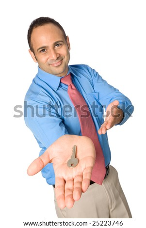 Happy young businessman handing viewer a key ( focus is on key )