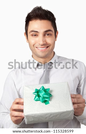 Happy young businessman  holding gift box isolated on white background. - stock photo