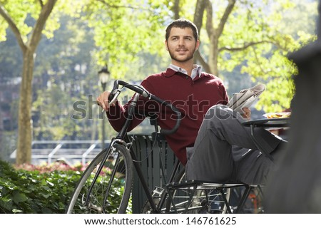 Happy young businessman holding newspaper by bicycle in park - stock photo
