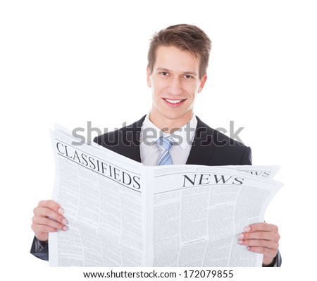 Happy Young Businessman Holding Newspaper Over White Background - stock photo