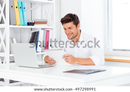 Happy young businessman holding notepad and looking at computer screen at the office