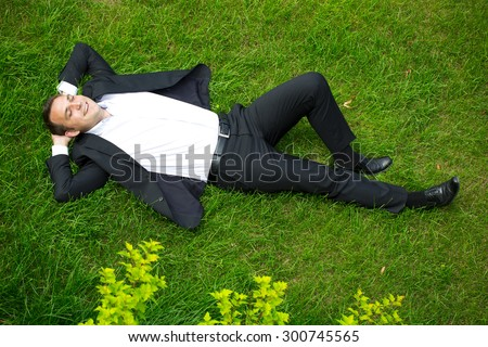 Happy Young businessman in a suit lying on the green grass, view from above - stock photo