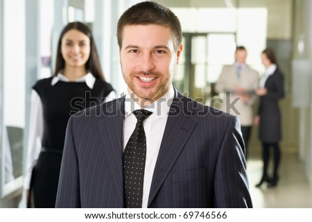 Happy young businessman  in an office environment - stock photo