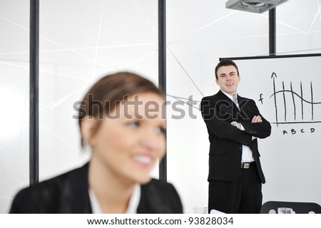 Happy young businessman in business presentation at office, looking at camera smiling - stock photo