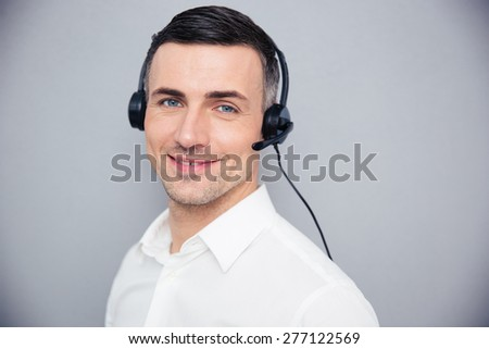 Happy young businessman in headphones over gray background. Looking at camera - stock photo