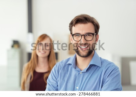 Happy Young Businessman Inside the Office, Wearing Blue Polo Shirt with Eyeglasses, Smiling at the Camera In Front his Female Co-worker.