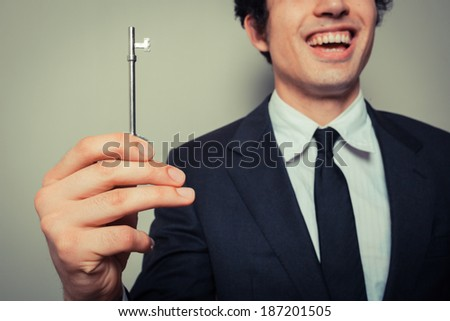Happy young businessman is holding a key and smiling - stock photo