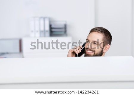Happy young businessman looking away while on call in office cubicle - stock photo