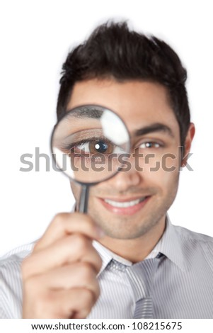 Happy young businessman looking through magnifying glass isolated on white background. - stock photo