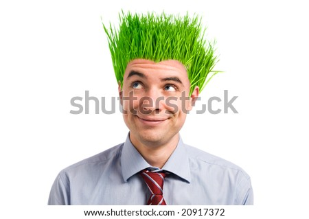 Happy young businessman looking up at his new vivid green grass hair. Green business concept - stock photo