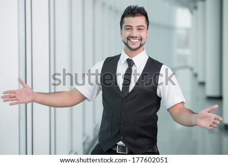 Happy young businessman of India spreading his hands apart to welcome - stock photo