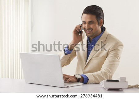 Happy young businessman on call while using laptop in office