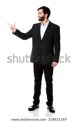 Happy young businessman points his finger to the left. - stock photo