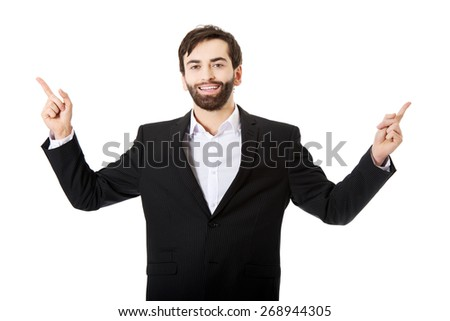 Happy young businessman points his finger up. - stock photo