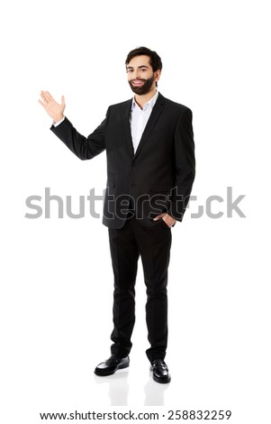 Happy young businessman presenting something. - stock photo