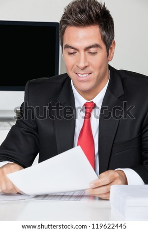 Happy young businessman reading document at desk in office - stock photo