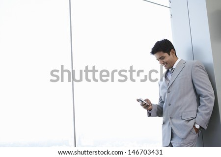 Happy young businessman reading text message on cell phone at office - stock photo