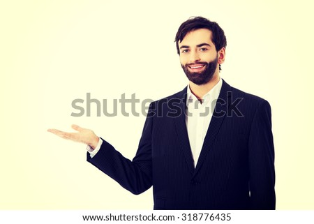 Happy young businessman showing empty copyspace on palm. - stock photo