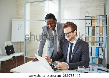 Happy young businessman showing his colleague information about new project - stock photo