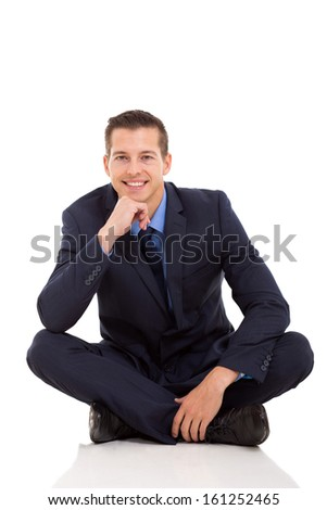 happy young businessman sitting on floor over white background - stock photo