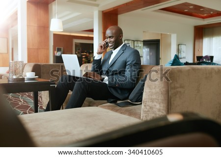 Happy young businessman sitting on sofa working using cell phone and laptop. African male executive waiting in hotel lobby. - stock photo