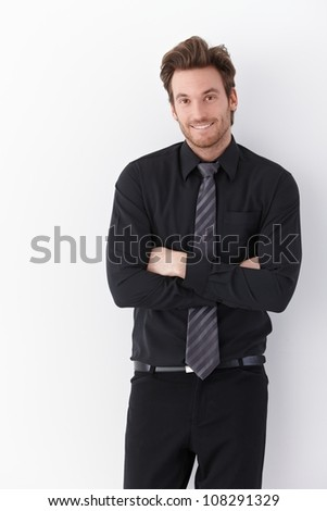 Happy young businessman standing arms crossed over white background. - stock photo
